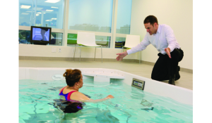 Physical therapist instructs a patient on an aquatic treadmill, one of the many forms of equipment that can help support the aquatic environment.