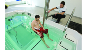 Physical therapist safely lowers a patient into the pool on an Aquatic Access chair.