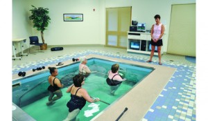 A staff instructor at Pieters Family Life Center guides a group class through aquatic-based exercise in the facility's HydroWorx pool. Water-based therapy, when performed in a specialized pool set at temperatures in the upper 80s or low 90s, is well-tolerated by people at every pain level.