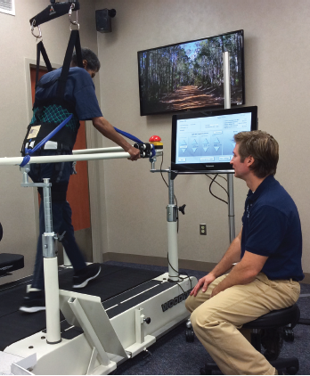 A therapist monitors a stroke patient who is using the Aretech ZeroG-Lite treadmill-based gait training system and the Woodway split-belt treadmill as a platform for gait training with error augmentation.