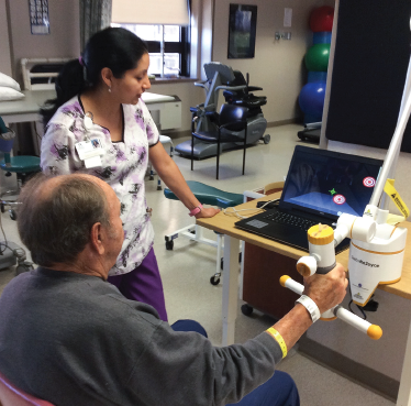 Therapist and patient using the Saebo ReJoyce with real-time error feedback and virtual reality interaction to assist with upper-extremity motor learning.
