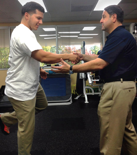 Author and patient work on balance testing as part of post-injury assessment.