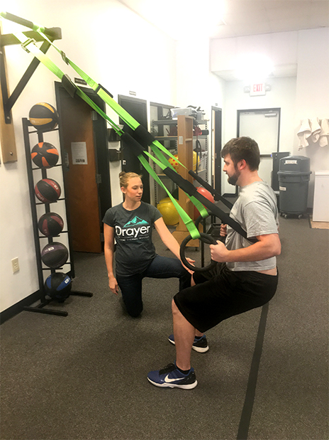 Therapist providing tactile cues to patient during squat on Primal 7.