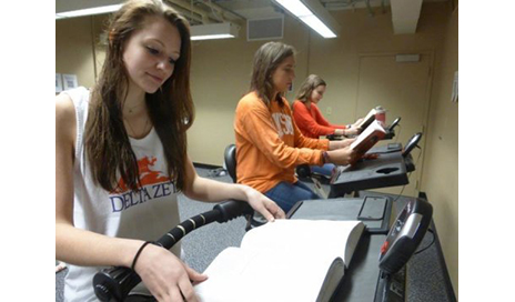 Clemson University students Sarah Limyansky, Jessica Cashman, and Vanessa Macpherson (left to right) read while pedaling at FitDesks. (Photo courtesy of June J. Pilcher)
