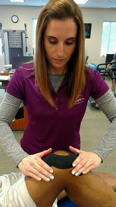 Sarah DoBroka, PT,SCS,COMT,Cert DN, applies therapeutic tape specifically cut and applied based on patient needs.