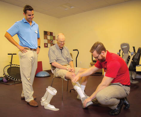 Physionetics therapist Shane Smith, PT, DPT, observes an orthotist evaluating a client for a solid ankle AFO to provide adequate toe clearance in swing phase and proper heel strike in initial stance phase of gait. This AFO also provides more stability to the ankle joint and promotes proper foot alignment upon weight bearing.