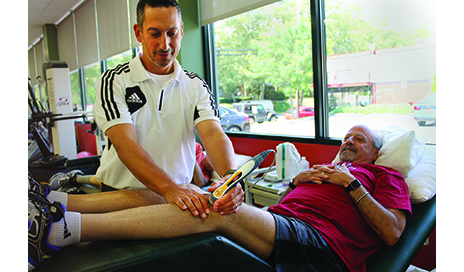Wil Siegel, PT, DPT, MBA, Cert MDT, site supervisor at Burke's Mamaroneck, NY, outpatient clinic, works with a patient using the cold laser (LLTT) for lower extremity pain management.
