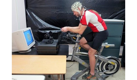 A participant in the UCSB study rides a stationary bicycle while wearing a wireless heart rate monitor and an EEG cap. (Image courtesy of University of California - Santa Barbara)