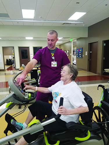 A patient with a primary diagnosis of chronic obstructive pulmonary disease (COPD) exacerbation and pneumonia works on cardiorespiratory endurance with her physical therapist, Ryan D. Morton, PT, DPT, using a recumbent cross trainer