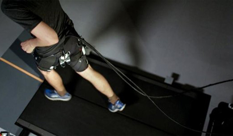 A treadmill runner demonstrates the use of the exosuit, which features a system of actuation wires attached to the back of it that provides assistive force to the hip joint during running. (Photo courtesy of The Wyss Institute at Harvard University)