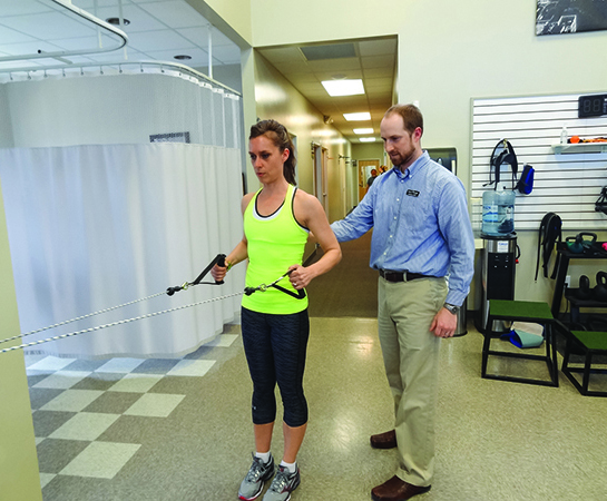 Andrew Hadrich, PT, DPT, guides a client through strengthening exercises using a Lojer cable column system. Among the accessories included with the system are benches, handles, straps, and bars that allow the cable columns to be used for every joint of the body.