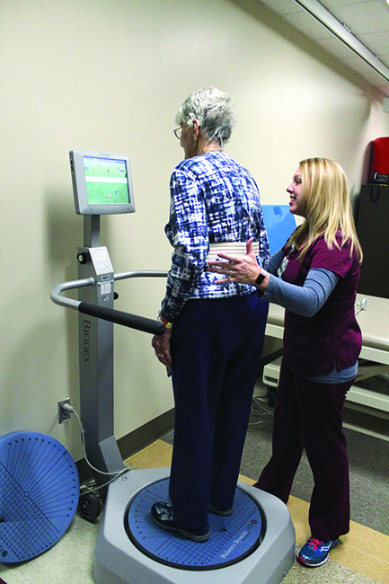 """A patient status post left hip hemi-arthroplasty practices the """"Ball Toss"""" game on the Biodex Balance System under the supervision of her  therapist, Leigh E. Whitton, PT, DPT."""