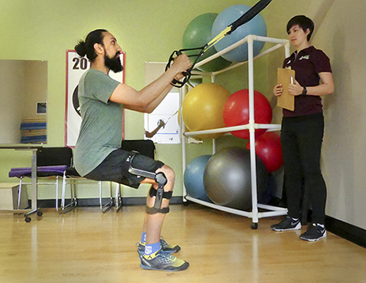 A therapist guides an athlete wearing a Levitation Knee Brace through a therapy session after knee injury. The brace features customizable force-output that can be tailored according to the user's requirements.