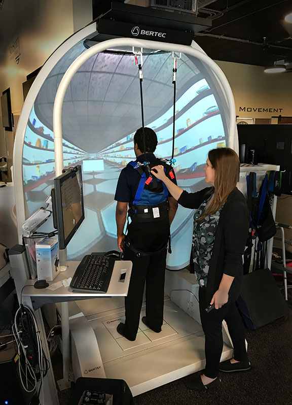 Therapist assists a client using immersive virtual reality with the Bertec Balance Advantage – Dynamic CDP at Movement First.