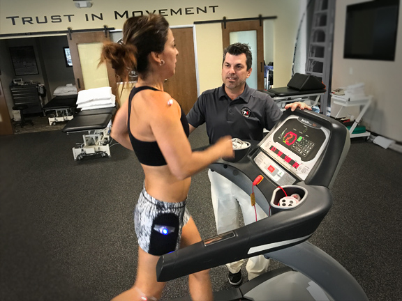 Brandon Dederich guides a client through a treadmill evaluation at Movement First. The client wears sensors that capture performance data recorded during the session.