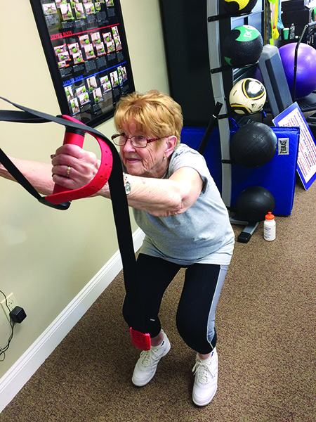 Doris, a PTW client, utilizes TRX straps to improve balance, quad strength, and sit to stand transfers without use of her bilateral armrests. Recently discharged, Doris is now an avid fitness member motivating people of all ages in the clinic.