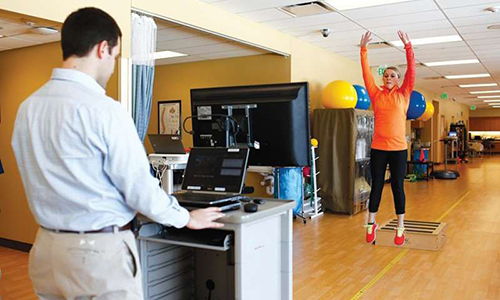 A participant in the motion capture study jumps off a platform while researcher Aaron Gray measures her biomechanics using a video game motion sensor. (Photo courtesy of Rachel Coward)