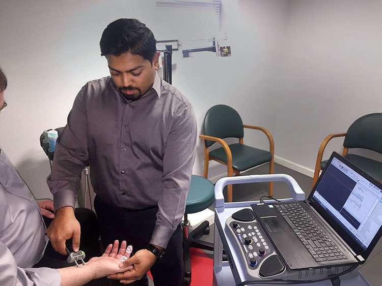 A median sensory nerve conduction study is being performed using Cadwell diagnostic system.
