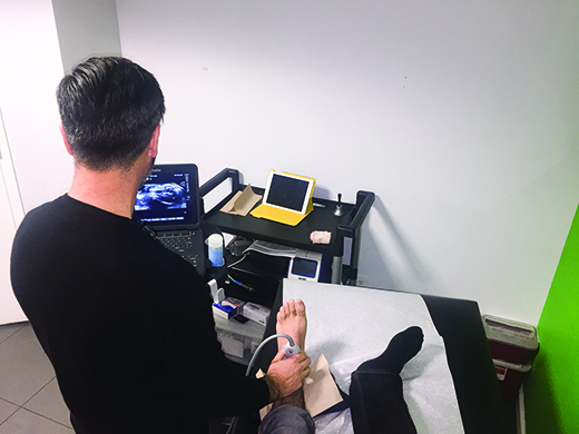 Clinician conducts a musculoskeletal ultrasound for further examination of the ankle joint to look for possibilities of tendonitis and abnormalities in the joint or surrounding tissues. The ultrasound provides real-time imaging as a way to improve diagnosis accuracy.