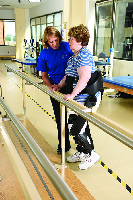 Overground robotic exoskeletons are worn on the outside of the user's body and expand the therapist's options for exercise and gait retraining. Pictured here, Clare Hartigan, PT, MPT, works with patient Patti Wise at Shepherd Center on improving gait and stability.