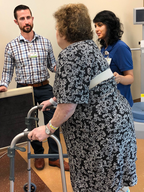Devin Breedon and a physical therapist discuss nutrition with a patient prior to discharge.