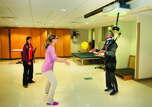 Amanda Charles, DPT, and Mary Noon, DPT, work on high level balance skills during a ball toss with a patient who has a spinal cord injury. The SafeGait 360º from Gorbel Medical, Victor, NY, provides dynamic support that allows the patient to explore his limits of stability without falling.