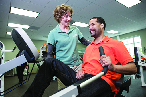 A Kessler Institute for Rehabilitation physical therapist cues a patient using the Nu-Step recumbent stepper.