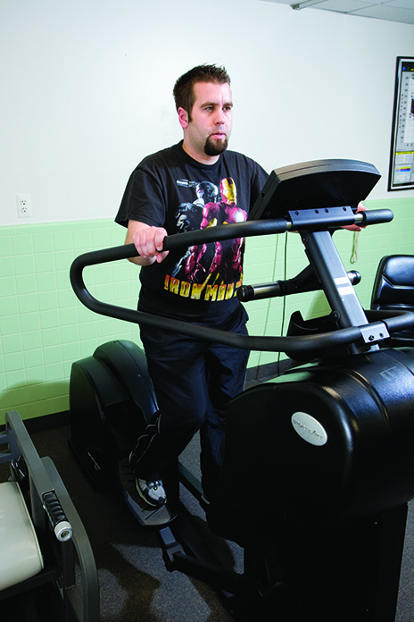 Patient working to build endurance on the SportsArt standing elliptical trainer.
